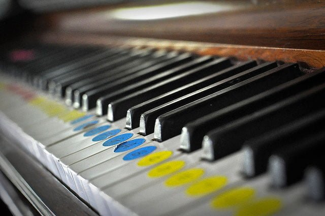 Close up of piano keys with colourful finger-guide stickers on the keys