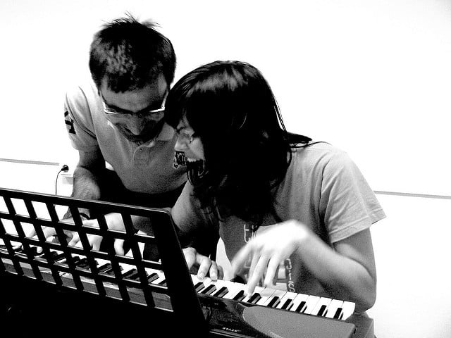 two adults playing a piano keyboard and laughing