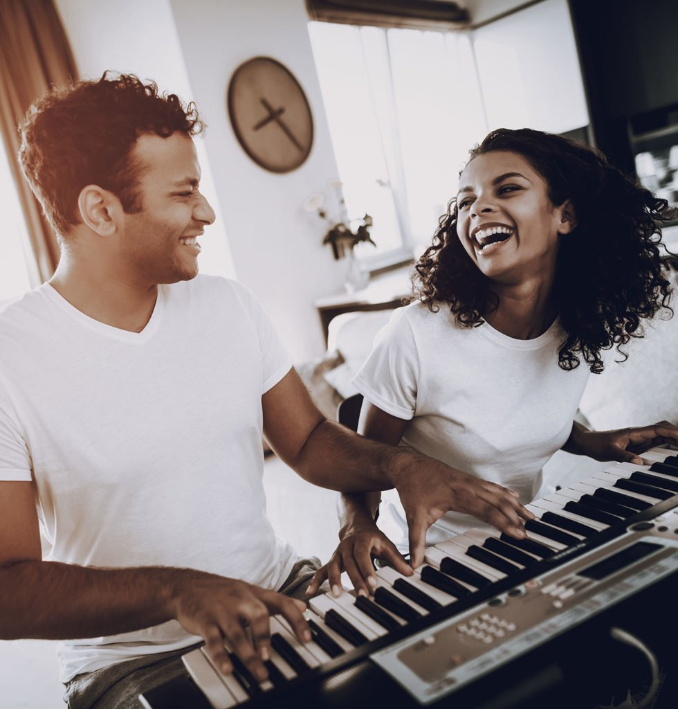 two adults smiling while playing a piano duet