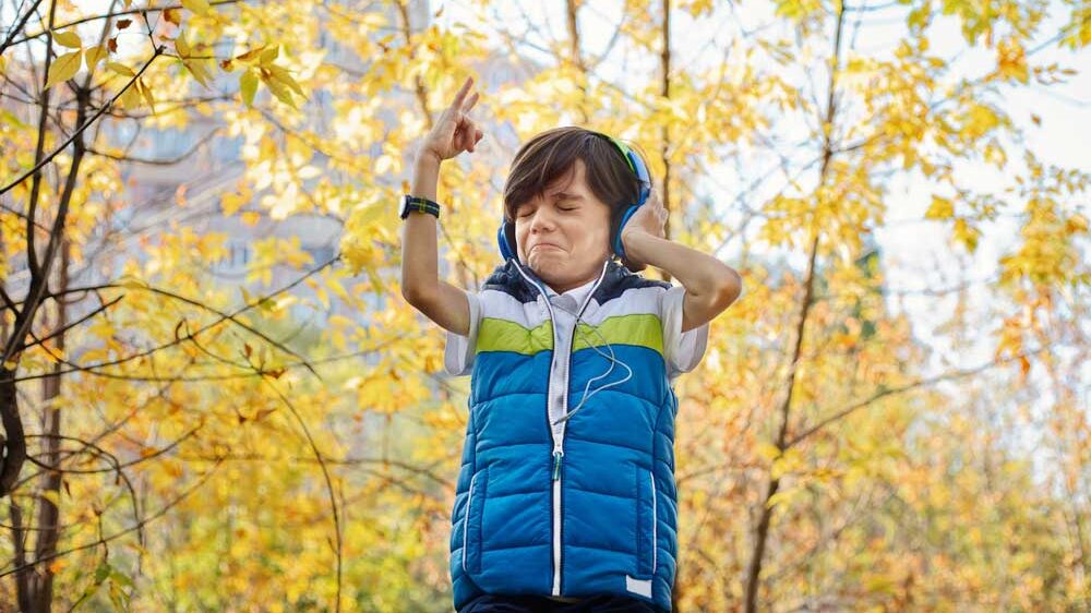 young boy listening to music on headphones throwing up his hand